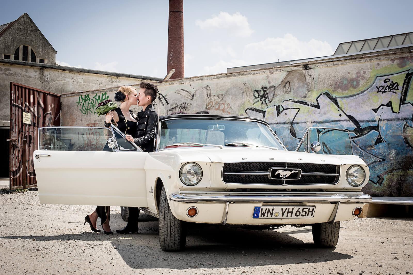 stylische Hochzeitsfotos in München - Hochzeitspaar mit Ford Mustang vor altem Fabrikgelände