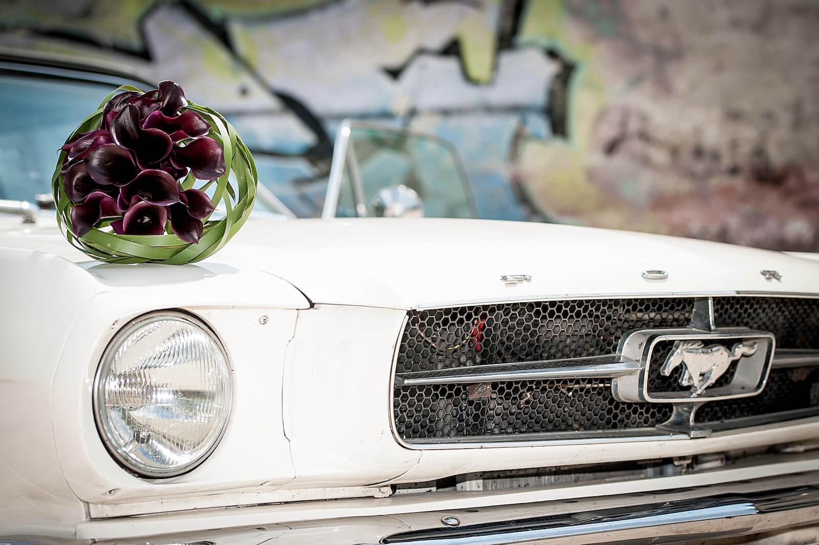 stylische Hochzeitsfotos in München - Hochzeitsstrauß auf dem Ford Mustang