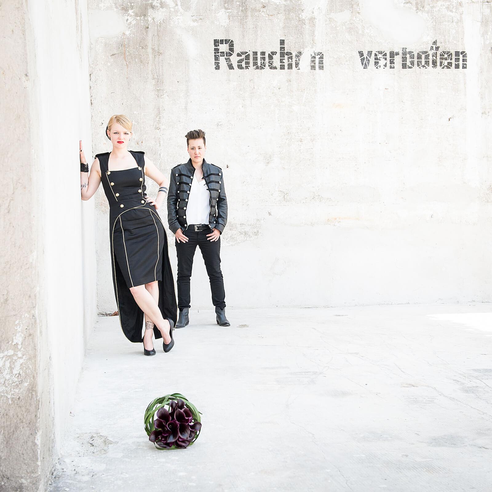 stylische Hochzeitsfotos in München - Hochzeitspaar vor Mauer mit Hinweis Rauchen verboten