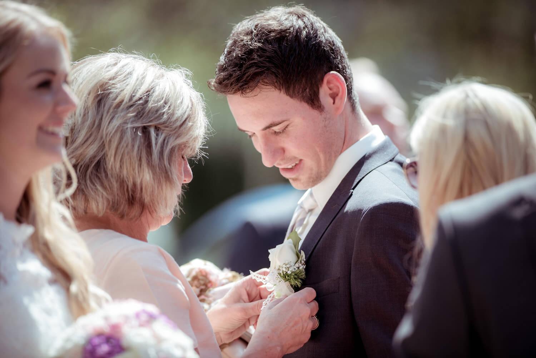 standesamtliche Trauung - Mutter richtet Boutonniere beim Bräutigam aus
