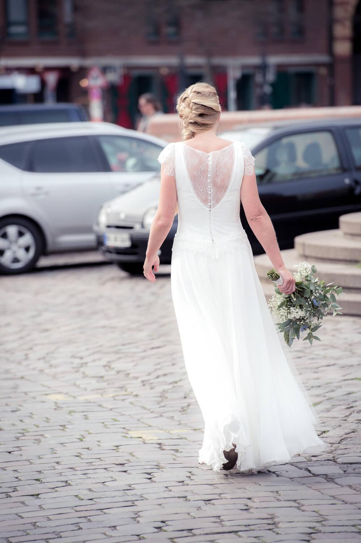 Hochzeitsfotografie - elegante Braut läuft über Kopfsteinpflaster
