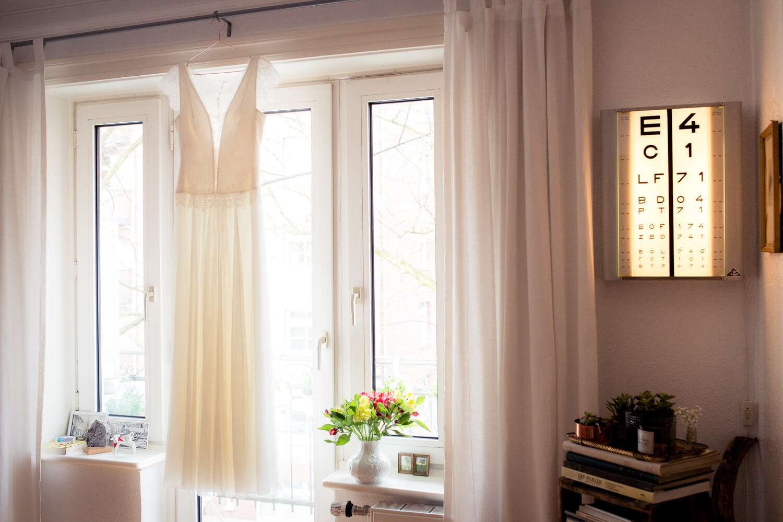 Hochzeitskleid hängt im Fenster in Hamburger Wohnzimmer