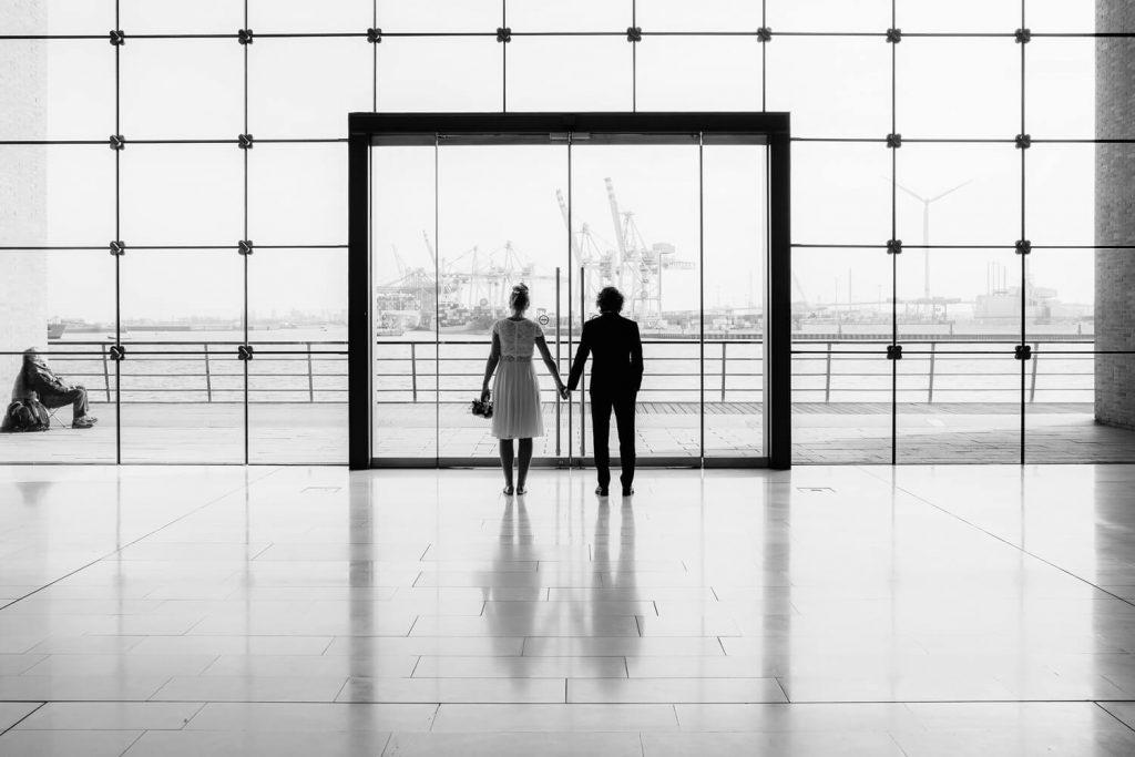 Hochzeit und Architektur - Braut und Bräutigam blicken auf Hamburger Hafen