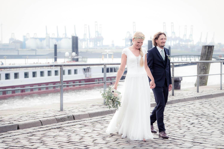 Hochzeitspaar schlendert vor Hamburger Hafenkulisse