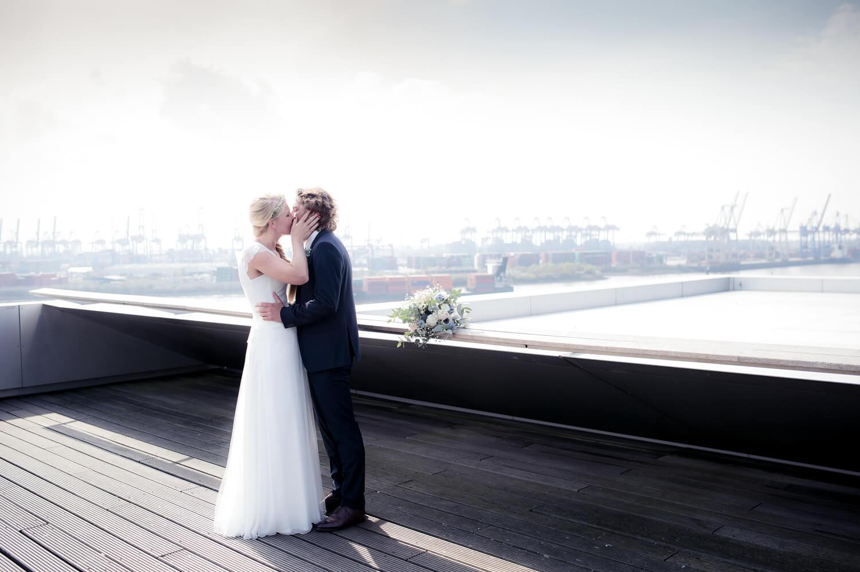 Hochzeitspaar küsst sich auf dem Dockland mit Blick auf die Elbe