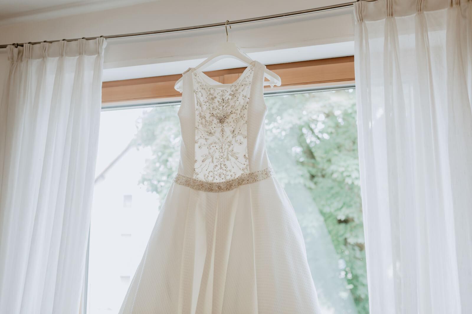 Gartenhochzeit Buchloe - Brautkleid im Fenster vor dem Anziehen