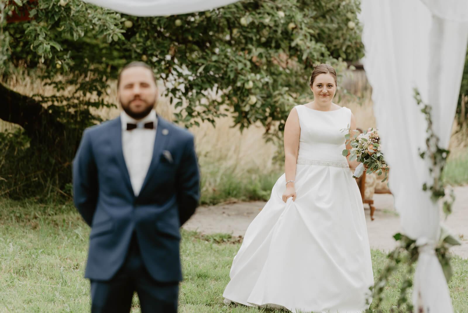 Gartenhochzeit Buchloe - first look, die Braut nähert sich dem Bräutigam
