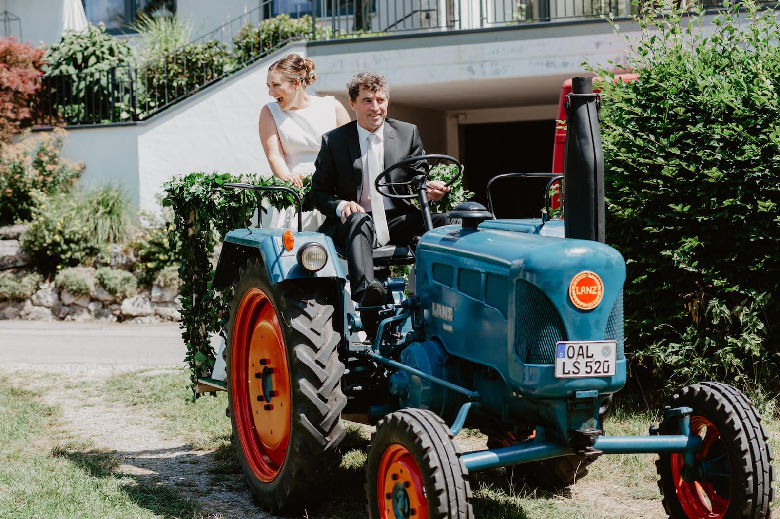Gartenhochzeit Buchloe - Einzug der Braut mit Vater auf einem Lanz Traktor