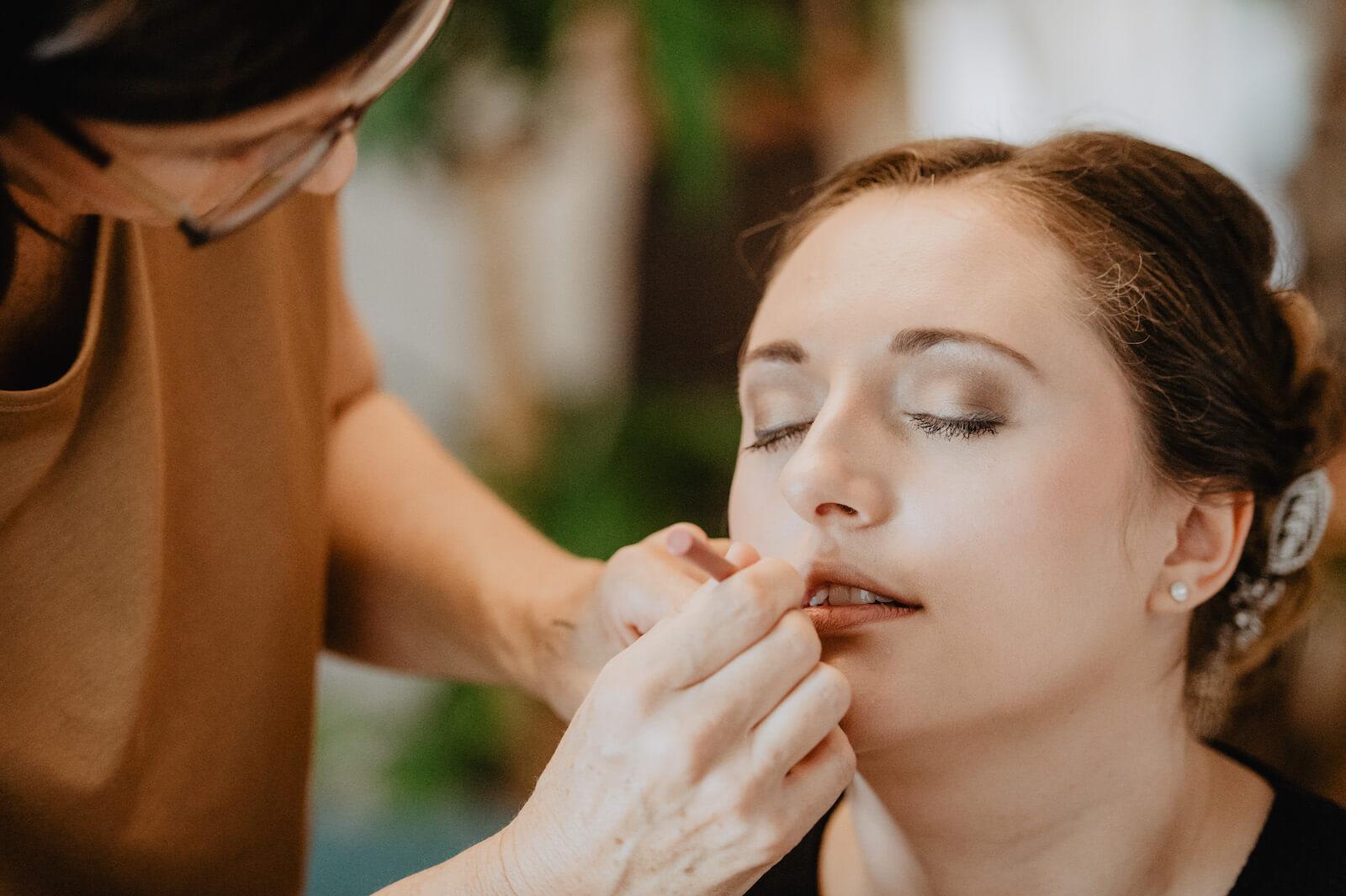 Gartenhochzeit Buchloe - Visagistin schminkt die Lippen der Braut