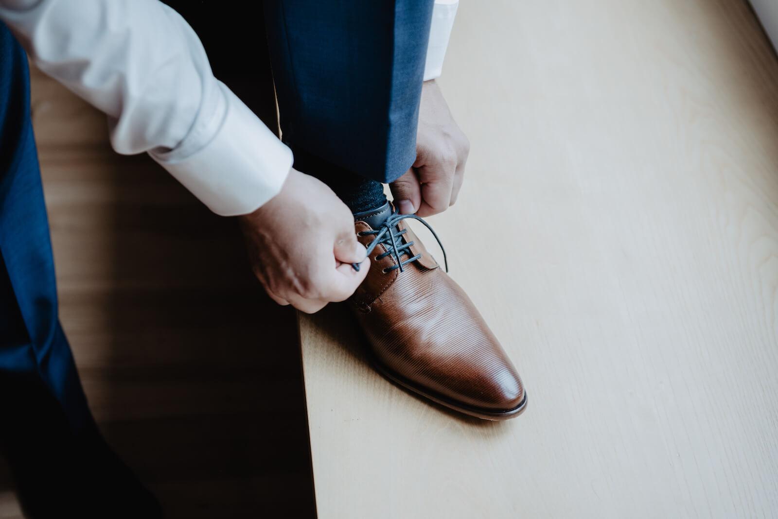 Gartenhochzeit Buchloe - Bräutigam bindet sich seine Schuhe
