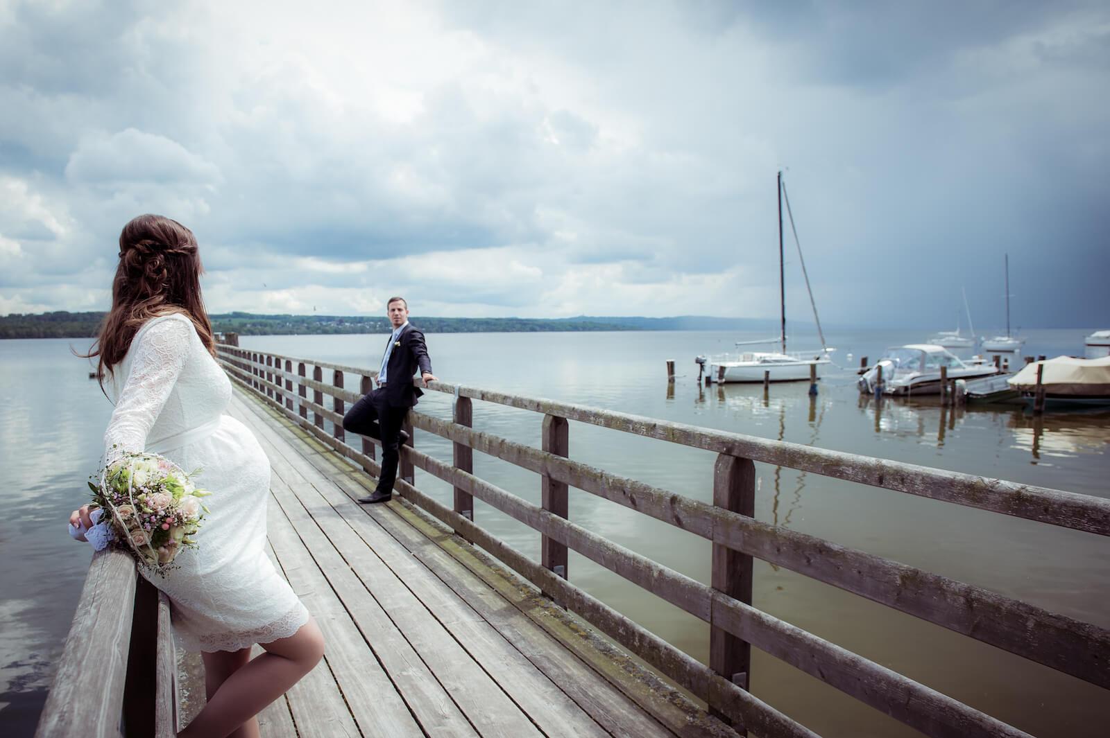 Hochzeit mit Babybauch - Hochzeitspaar auf dem Steg am Ammersee bei Gewitterstimmung