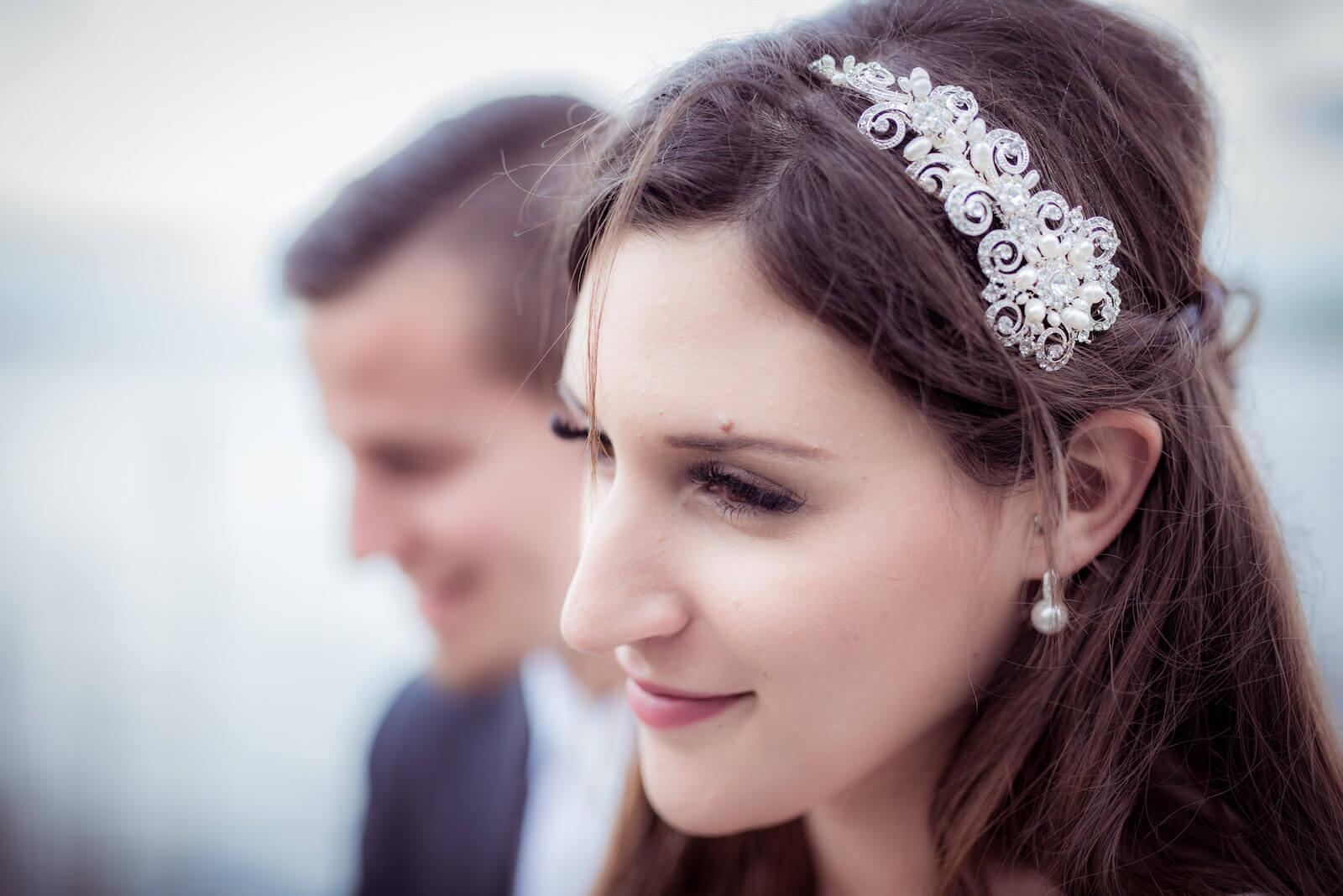 Hochzeit mit Babybauch - Braut im Portrait, im Hintergrund der Bräutigam