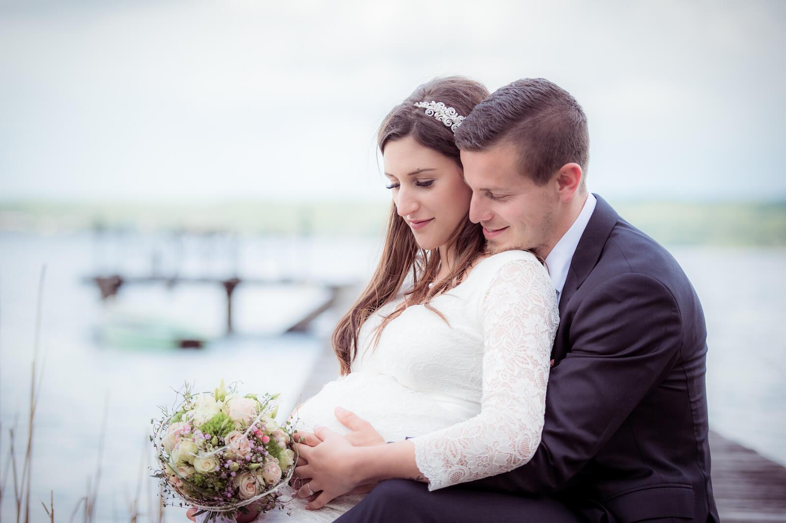 Hochzeit mit Babybauch - das Brautpaar am Ufer des Ammersee sitzend am Steg