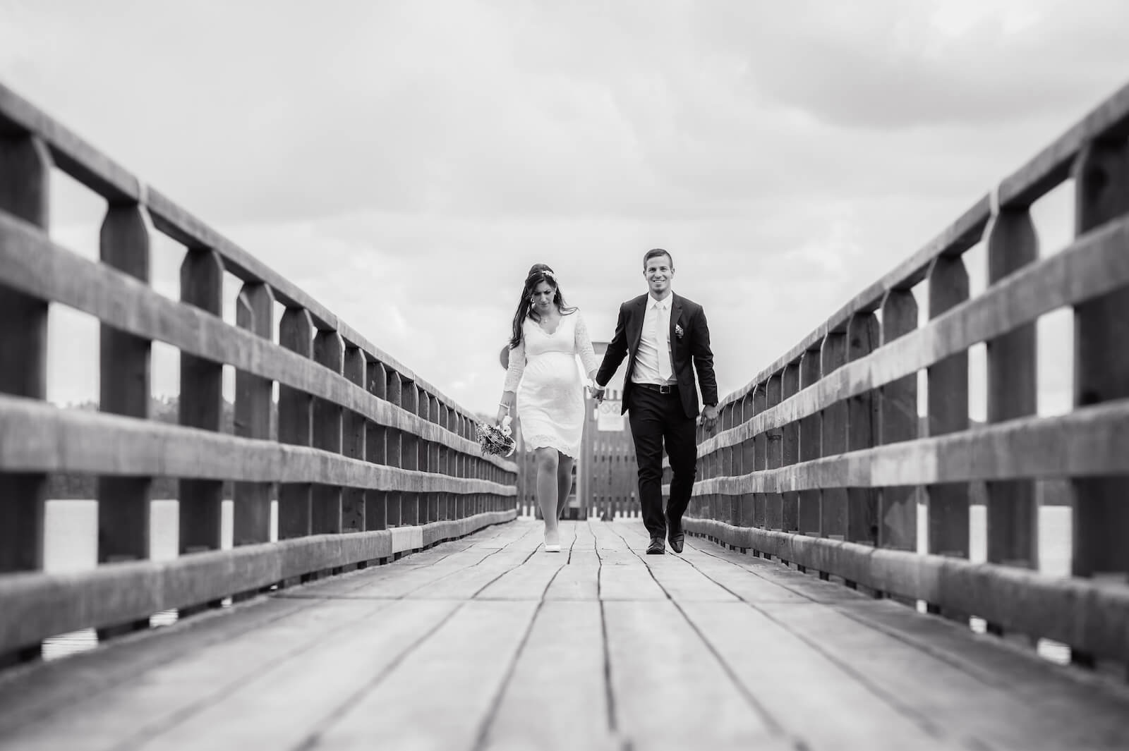 Hochzeit mit Babybauch - Braut und Bräutigam laufen auf einem Steg am Ammersee