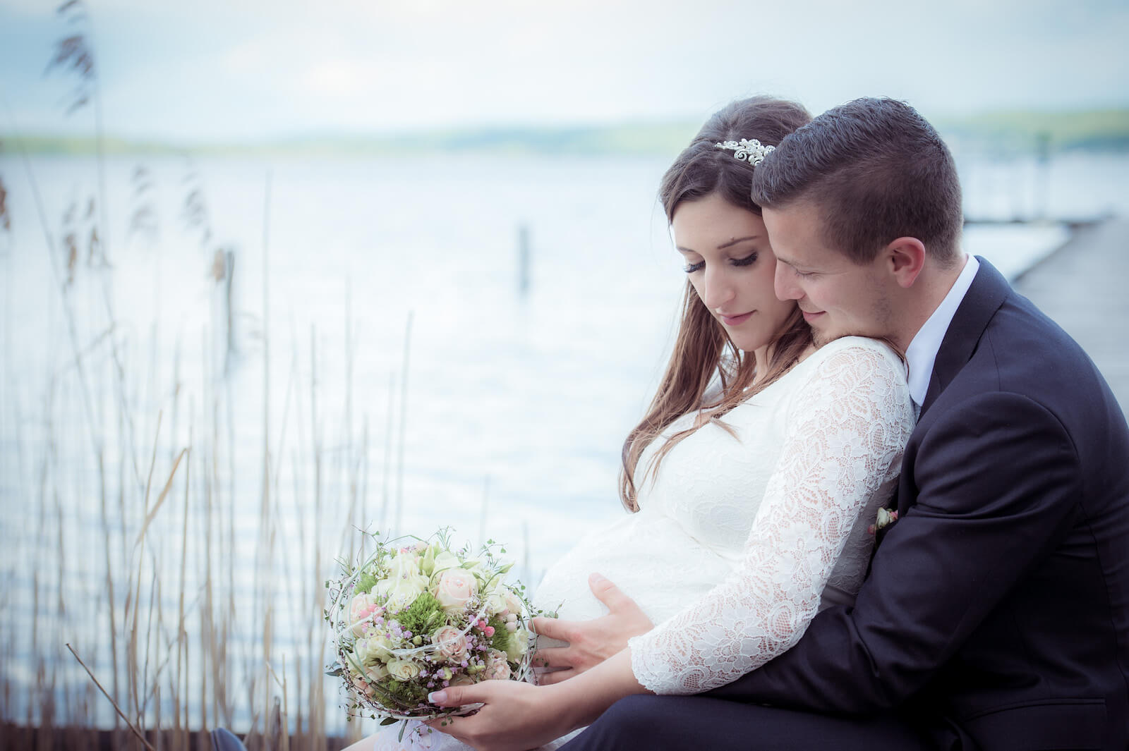 Hochzeit mit Babybauch - Braut und Bräutigam sitzen auf Steg am Ammersee