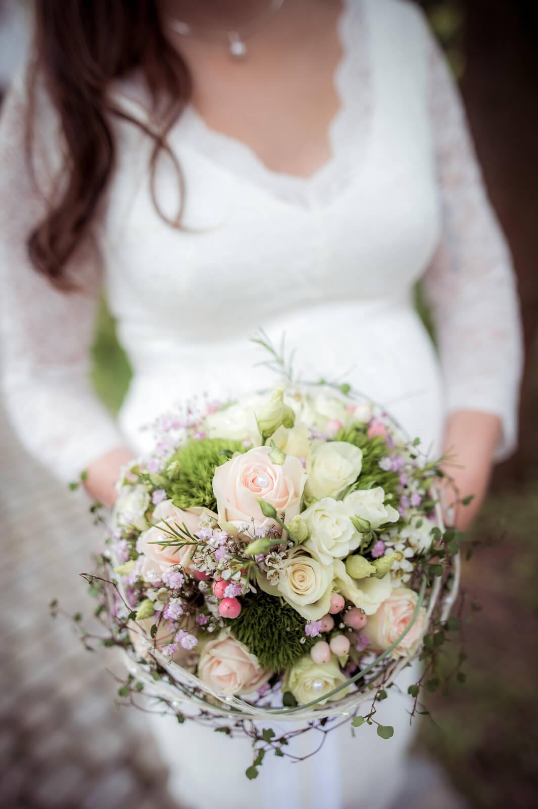 Hochzeit mit Babybauch - der Hochzeitsstrauß in Händen der schwangeren Braut