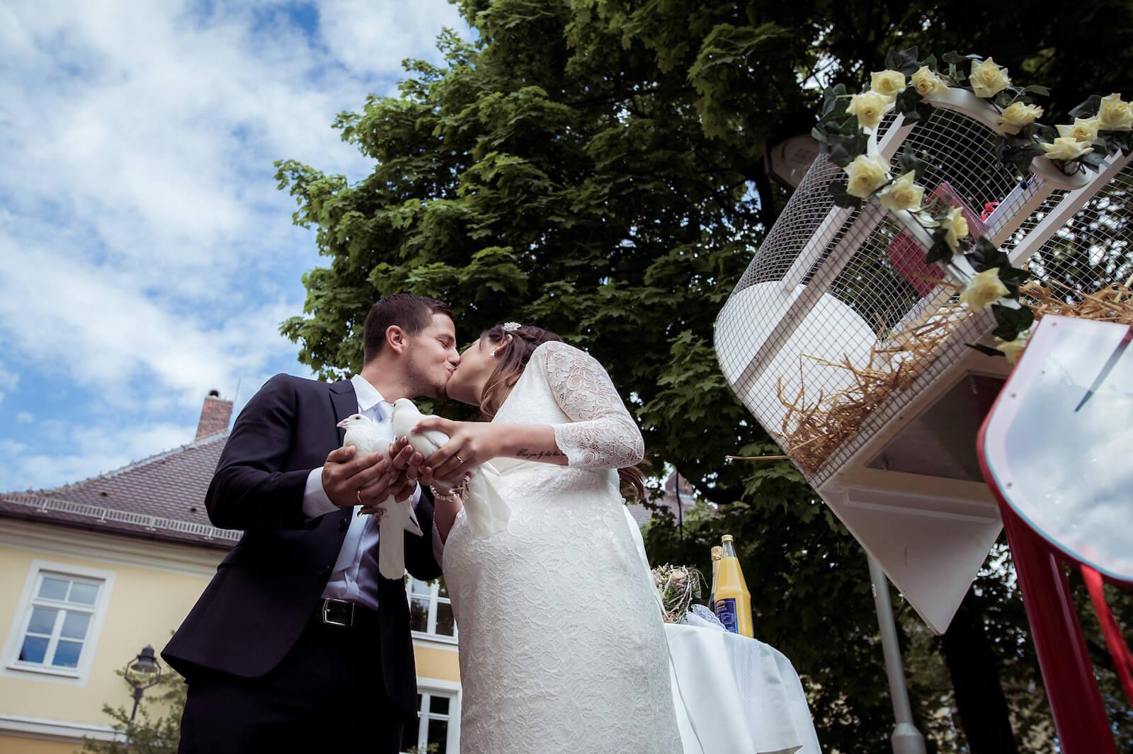 Hochzeit mit Babybauch - das Brautpaar mit weißen Tauben in der Hand