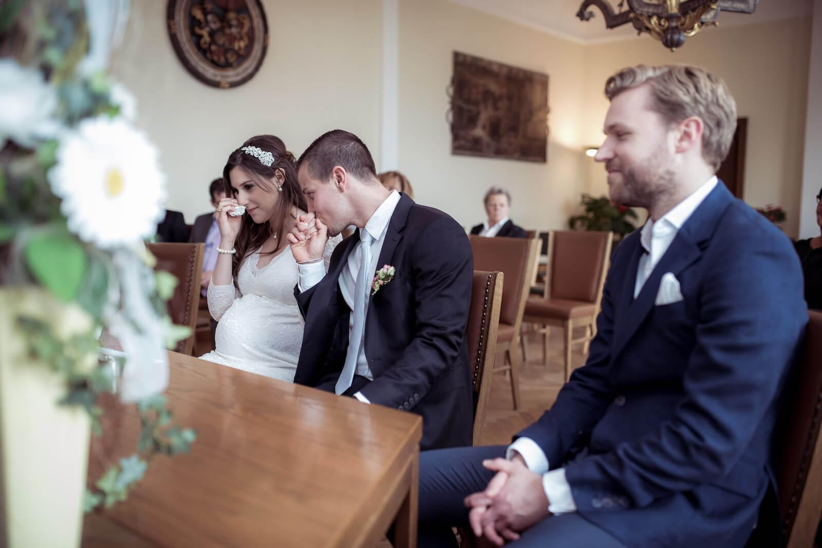 Hochzeit mit Babybauch - Braut im Standesamt wischt sich Träne aus dem Auge