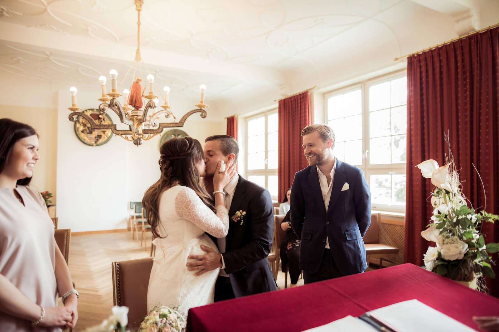 Hochzeit mit Babybauch - das Brautpaar küsst sich nach dem Ja-Wort im Standesamt