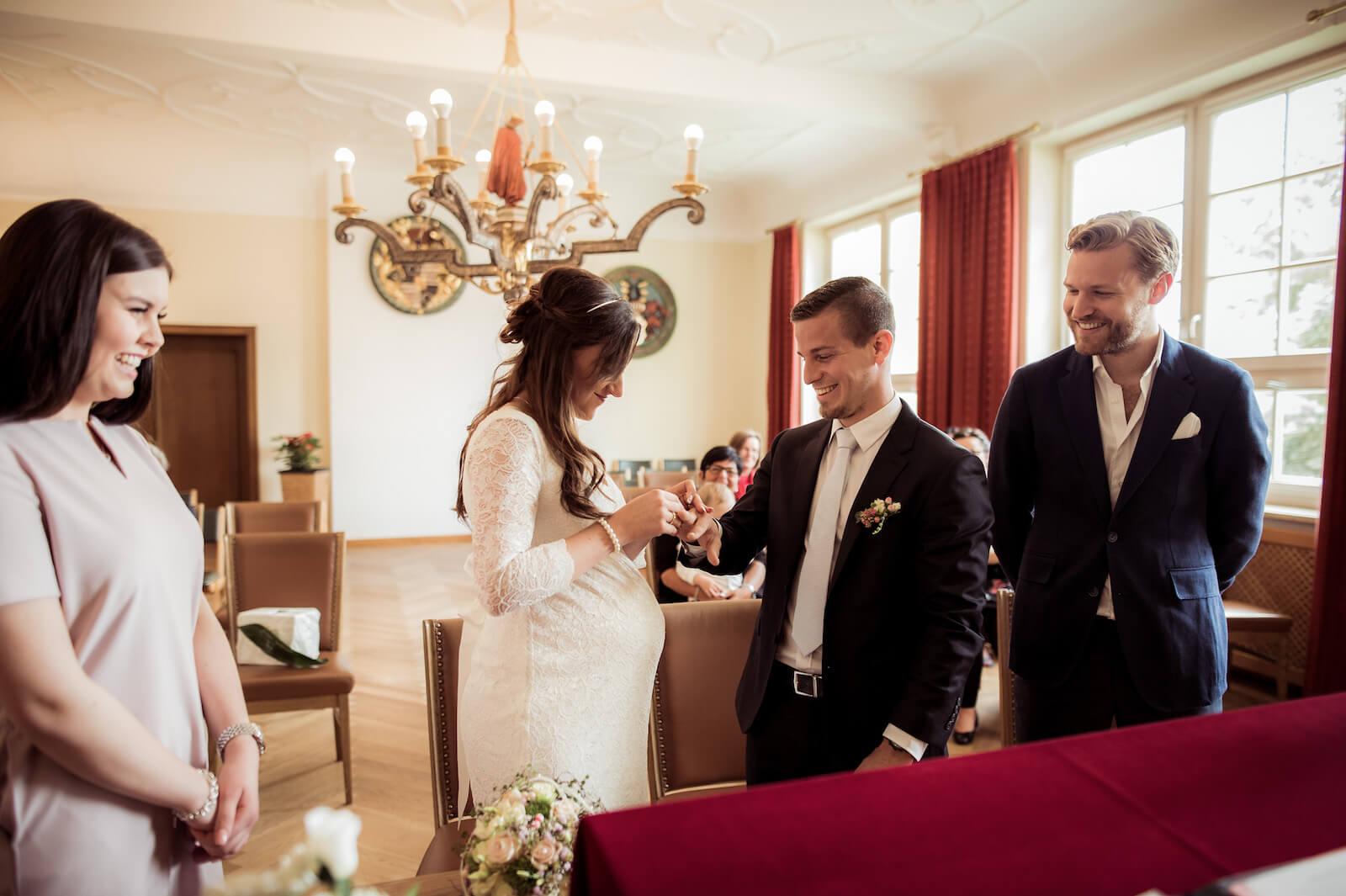 Hochzeit mit Babybauch - Braut steckt dem Bräutigam den Ring an