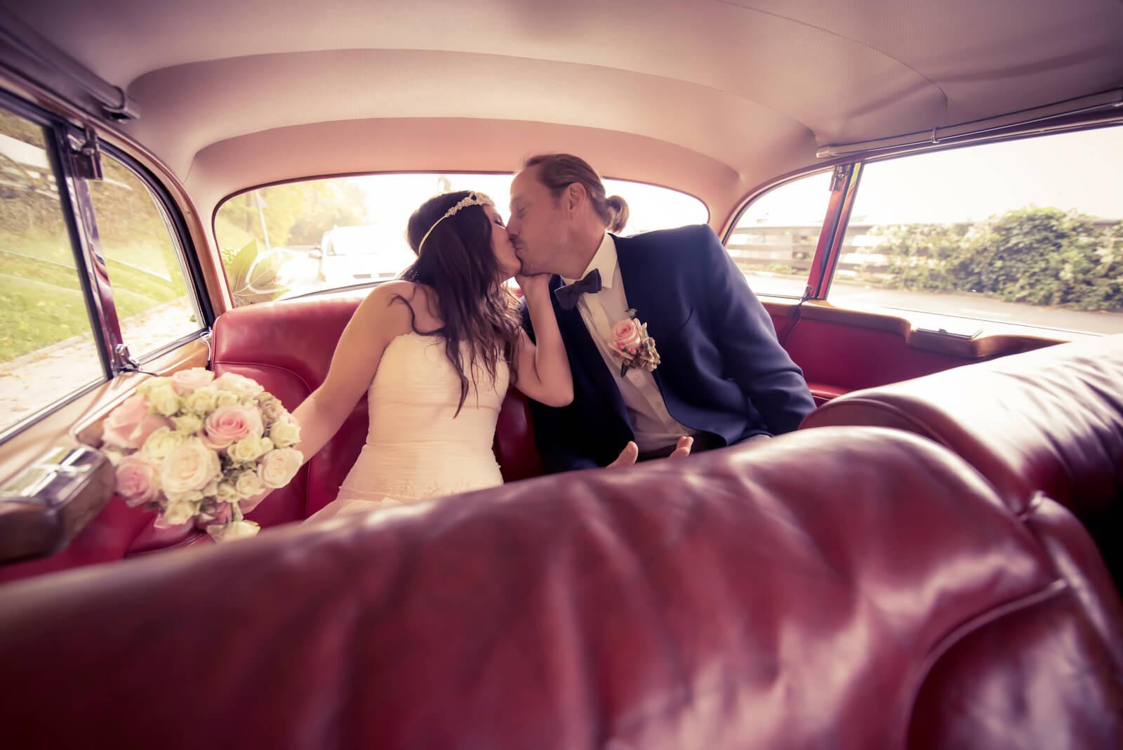 Hochzeit Bohostyle Landsberg - das Brautpaar küsst sich im Fond eines Mercedes W189