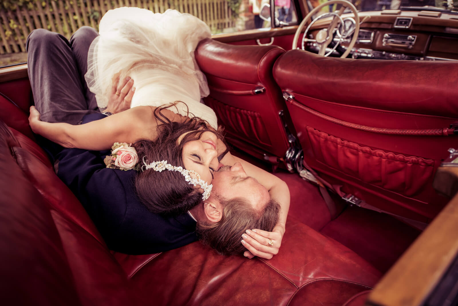 Hochzeit Bohostyle Landsberg - das Brautpaar liegt im Fond eines Mercedes W189