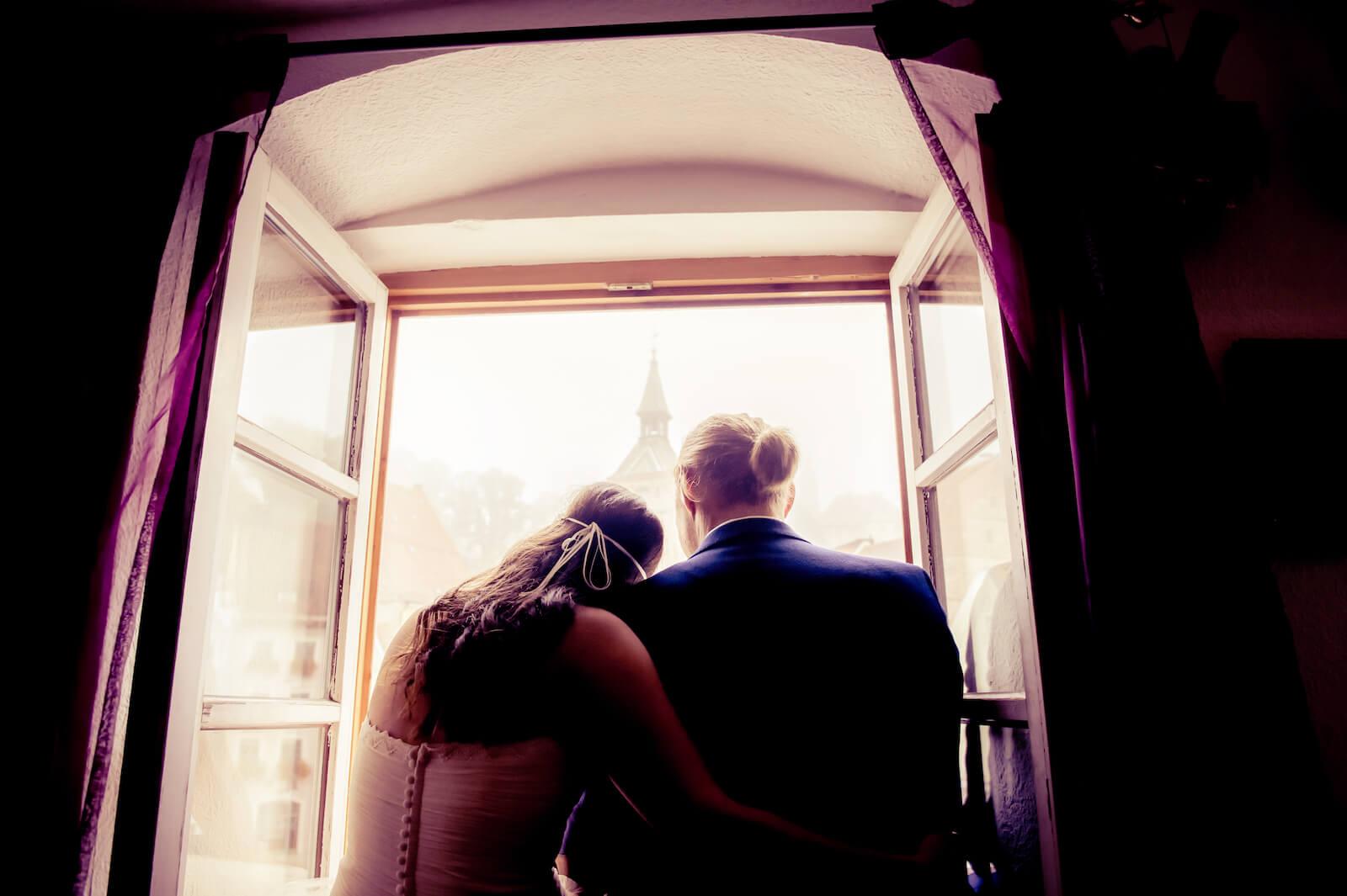Hochzeit Bohostyle Landsberg - das Brautpaar sitzt im Fenster ihrer Altstadtwohnung