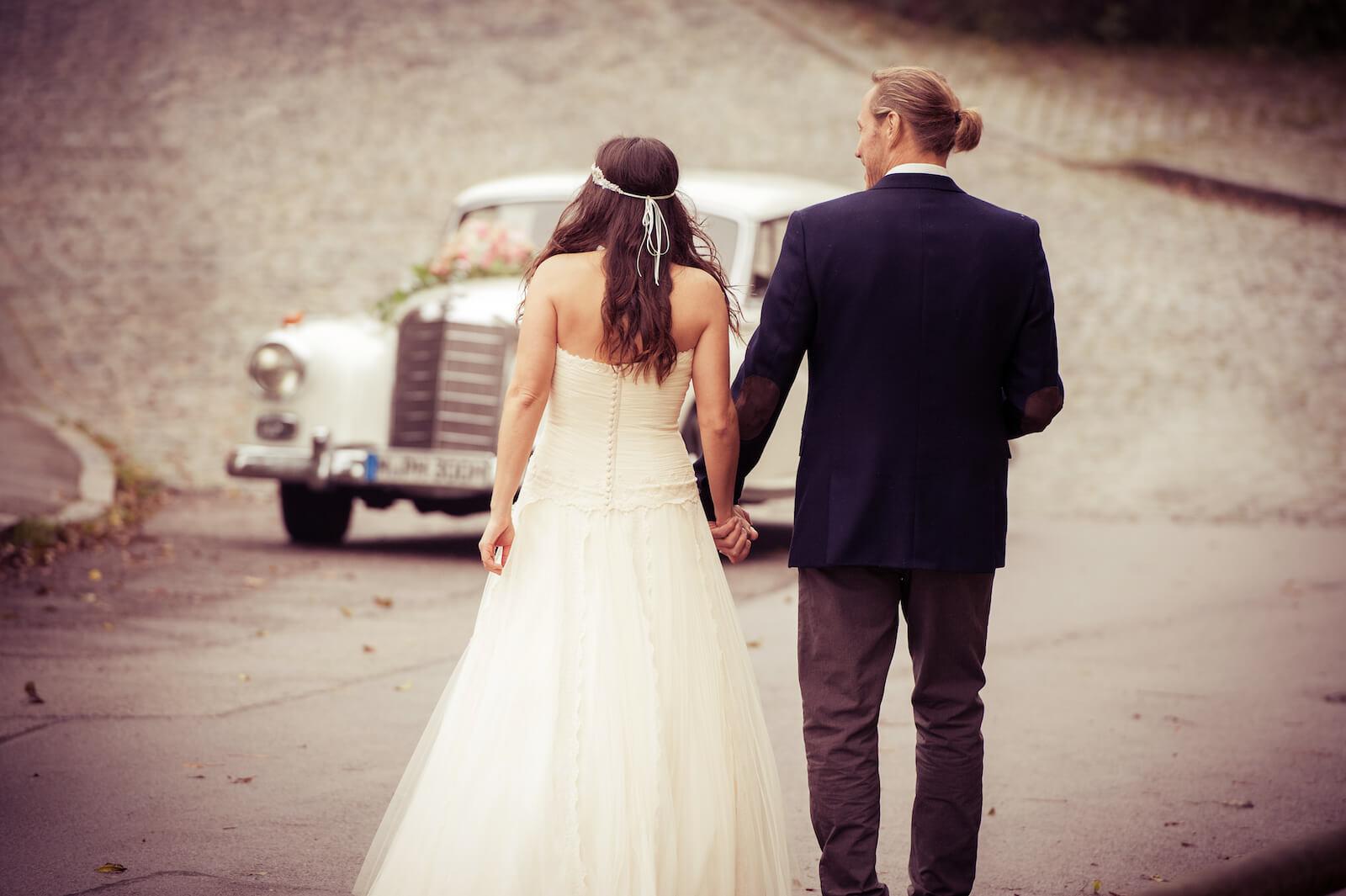 Hochzeit Bohostyle Landsberg - das Brautpaar geht zum Hochzeitsauto, ein Mercedes 300 W189