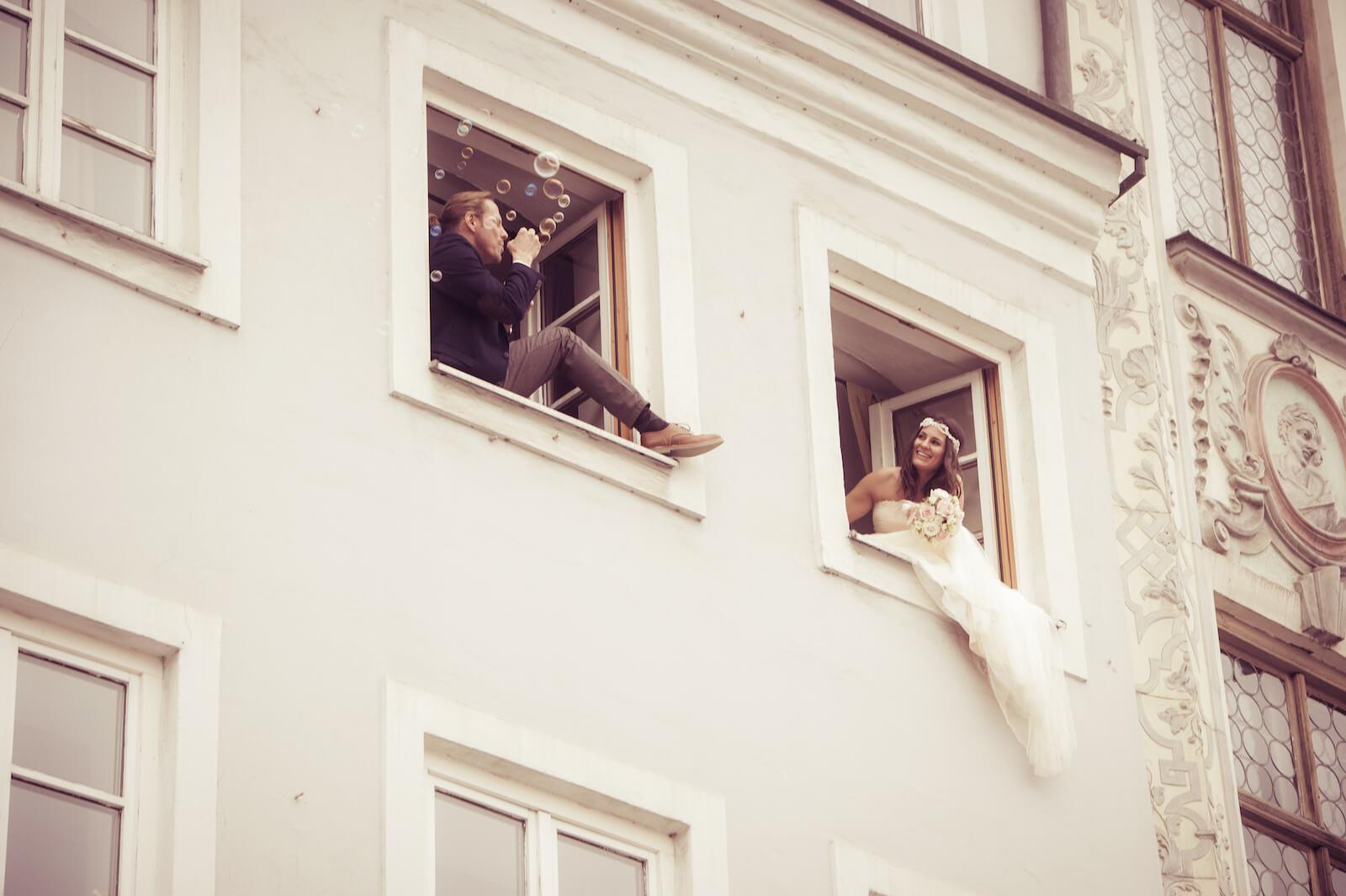 Hochzeit Bohostyle Landsberg - das Brautpaar in zwei Altstadtfenstern, der Bräutigam bläst Seifenblasen