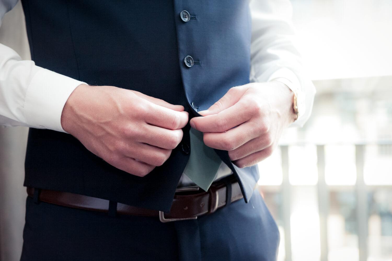 Hochzeit - Bräutigam knöpft sich die Weste