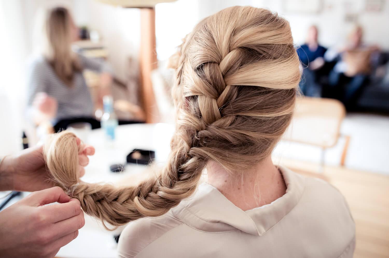 Hochzeitsfotografie - Haare der Braut werden zu einem Zopf gebunden