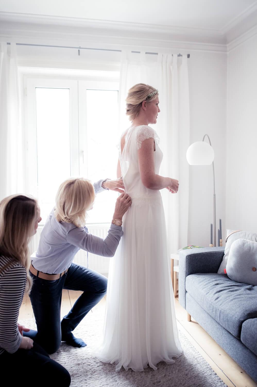 Hochzeit getting ready - Mutter und Trauzeugin knöpfen das Brautkleid zu