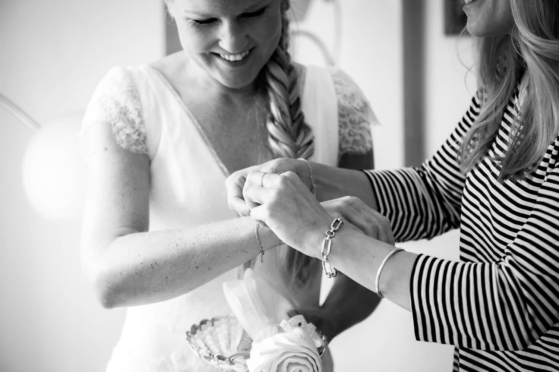 Hochzeit getting ready - Trauzeugin legt Braut das Armkettchen an