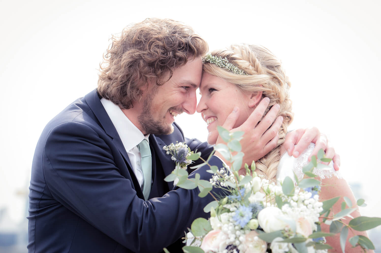 wunderschöner Moment des Glücks - Bräutigam umarmt liebevoll seine Braut