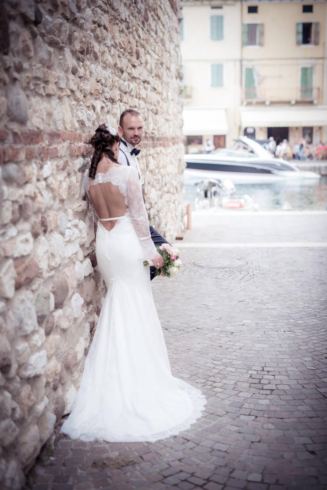 Hochzeit Gardasee - Brautpaar in alter Gasse, im Hintergrund der Hafen