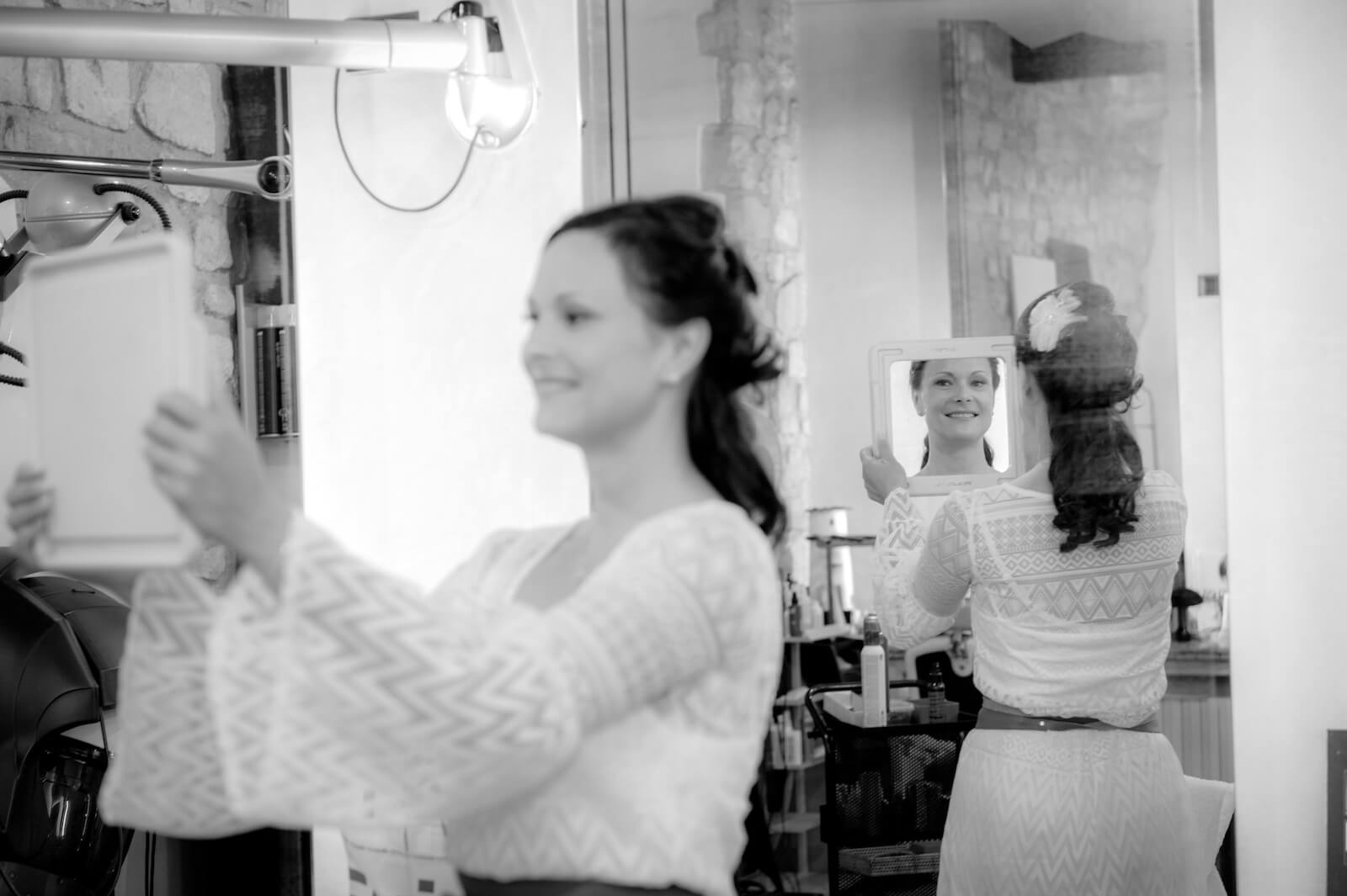 Hochzeit Gardasee - die Braut betrachtet sich im Spiegel beim Friseur
