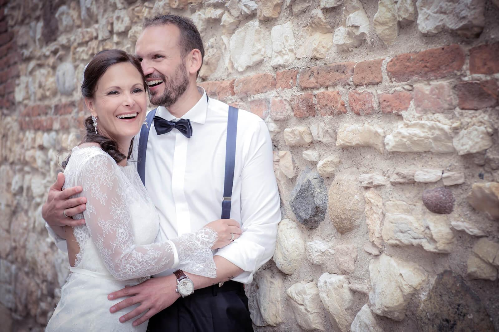 Hochzeit Gardasee - Hochzeitspaar an antiker Mauer in Lazise