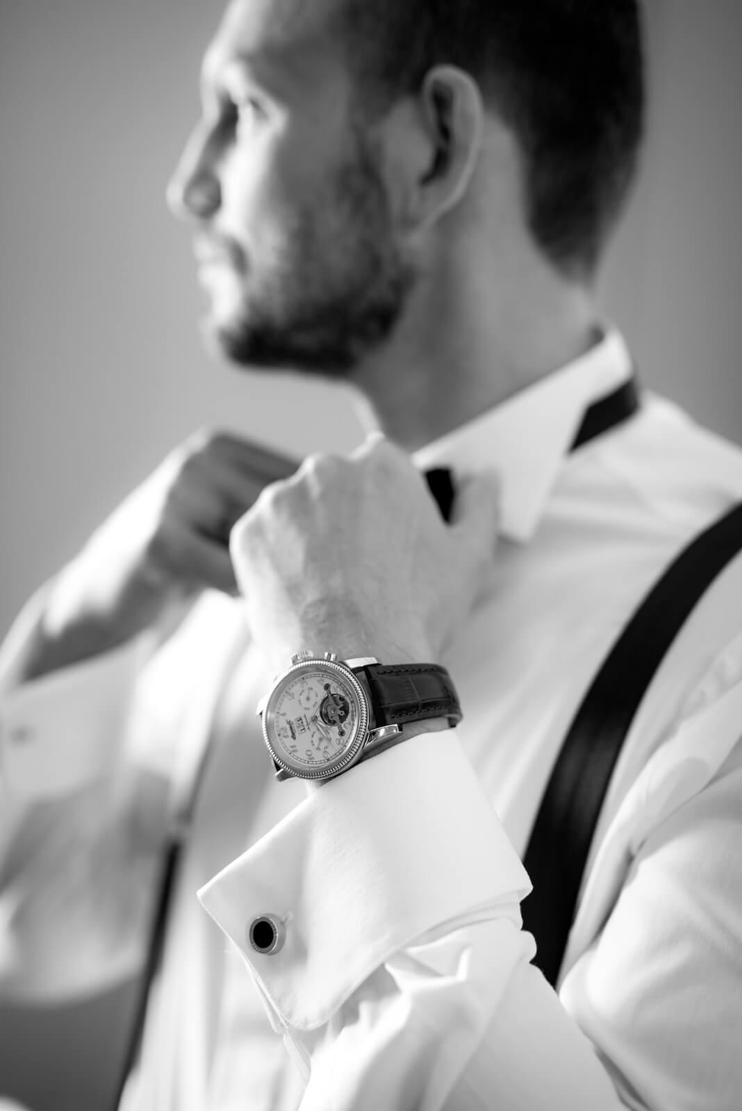 Hochzeit Gardasee - Bräutigam richtet seine Fliege aus, im Vordergrund seine Uhr