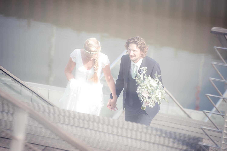 Hochzeitspaar steigt die Treppe am Dockland hinauf