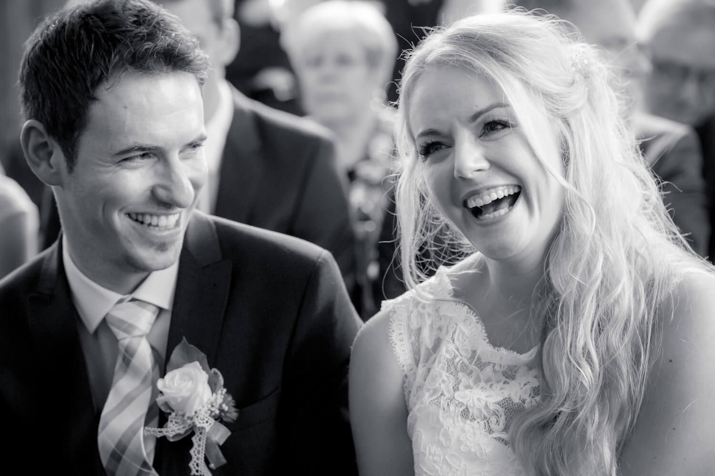 standesamtliche Trauung - Hochzeitsfotograf fängt lachendes Brautpaar im Standesamt ein