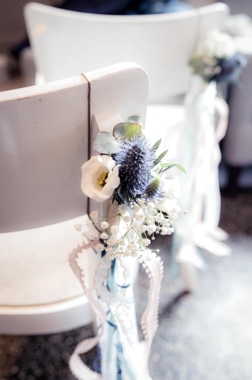 Hochzeitsfotografie - Nahaufnahme einer Blumendeko am Stuhl