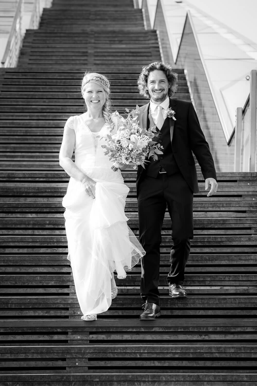 Hochzeitsbilder - glückliches Brautpaar geht Treppe hinab