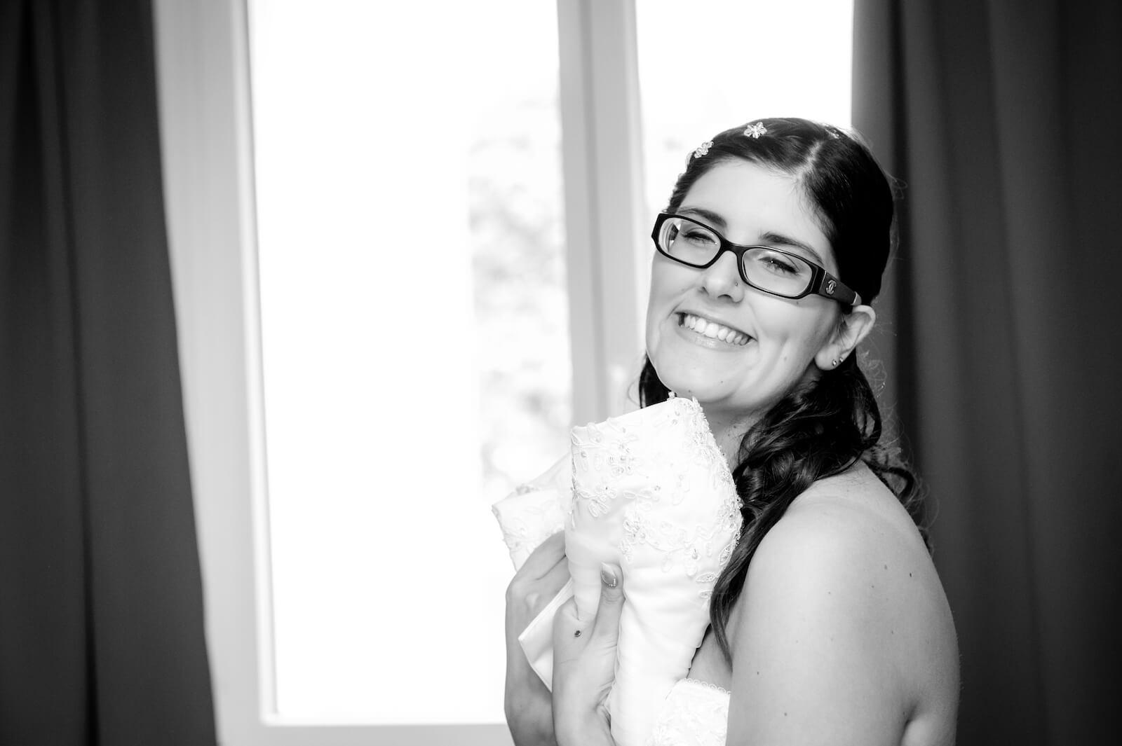 kirchliche Trauung in Landsberg - Braut freut sich während dem Anziehen des Brautkleides