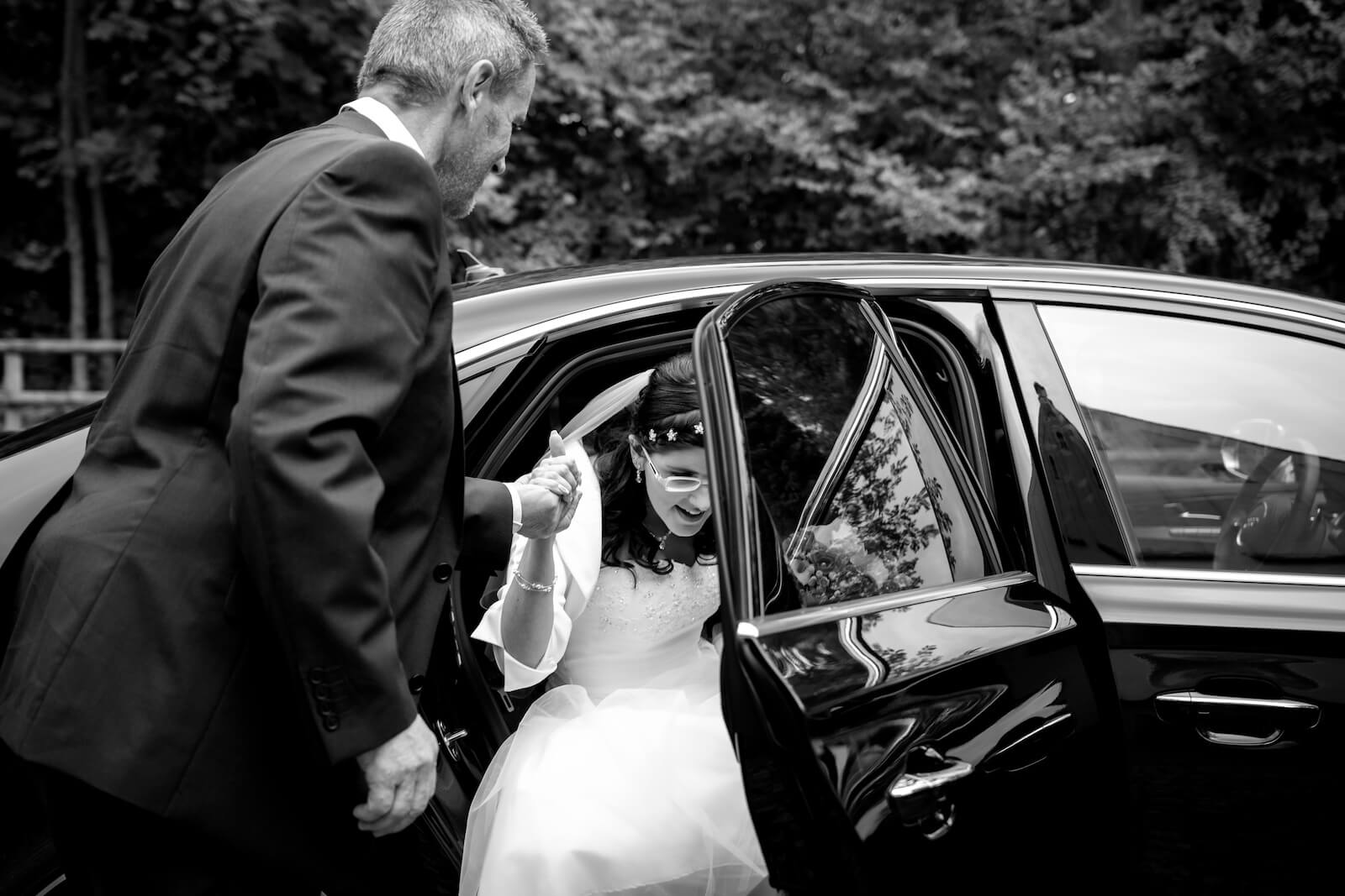 kirchliche Trauung in Landsberg - Braut steigt mit Hilfe des Vaters aus dem Hochzeitsauto