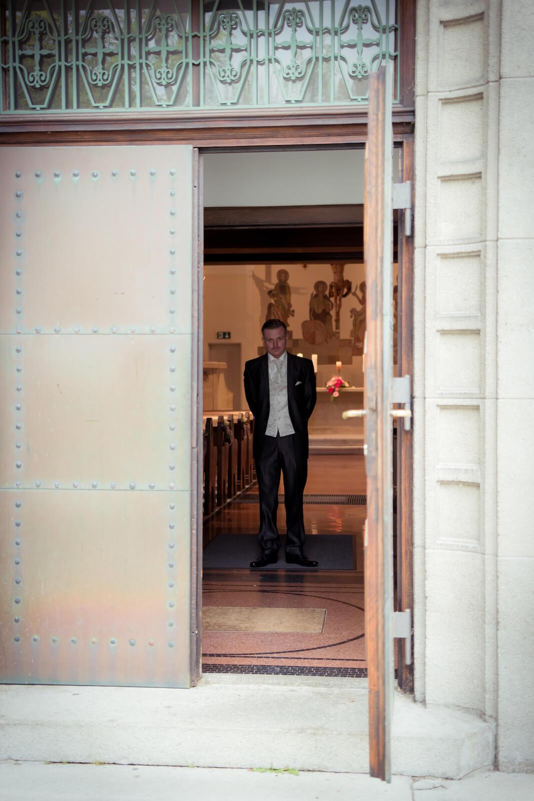 kirchliche Trauung in Landsberg - Bräutigam steht erwartungsvoll im Eingang der Kirche