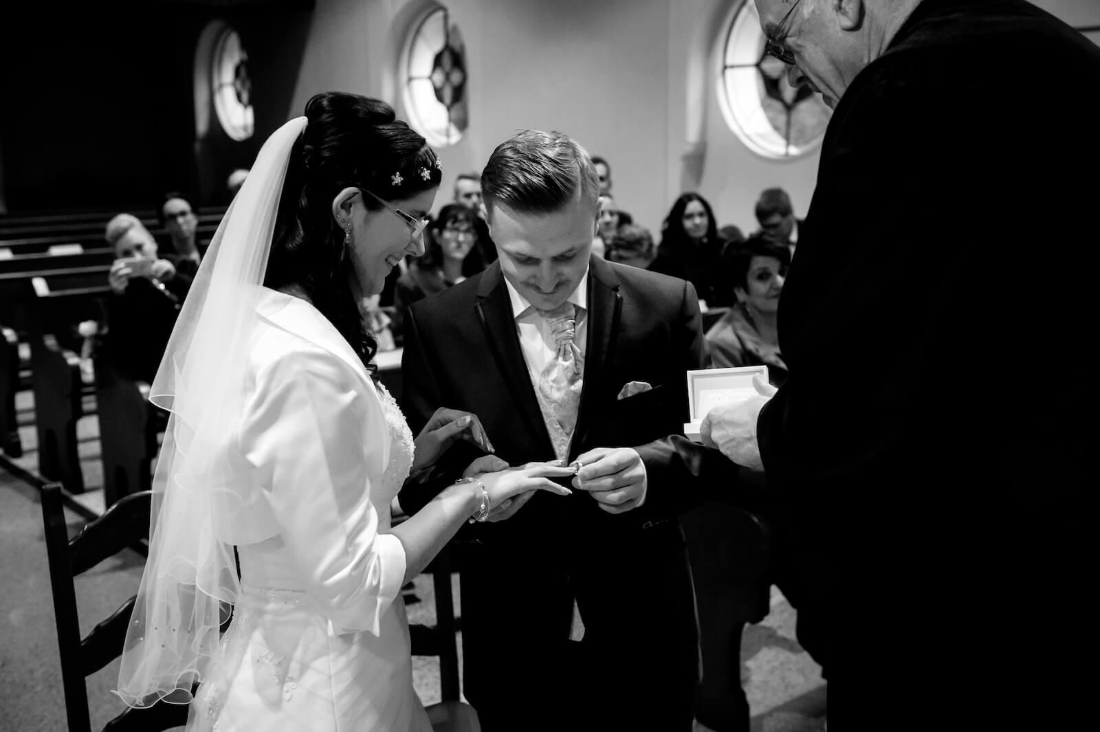 kirchliche Trauung in Landsberg - Bräutigam steckt Braut den Ring in der Kirche an