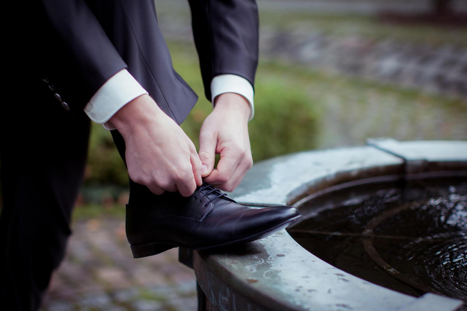 kirchliche Trauung in Landsberg - Bräutigam schnürt sich seine Schuhe am Brunnen