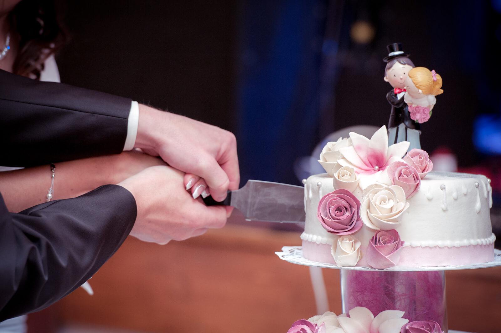 kirchliche Trauung in Landsberg - Brautpaar schneidet Hochzeitstorte an