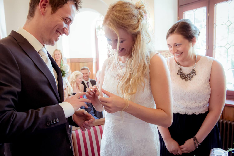 standesamtliche Trauung - Braut steckt Bräutigam den Ehering an, Trauzeugin im Hintergrund