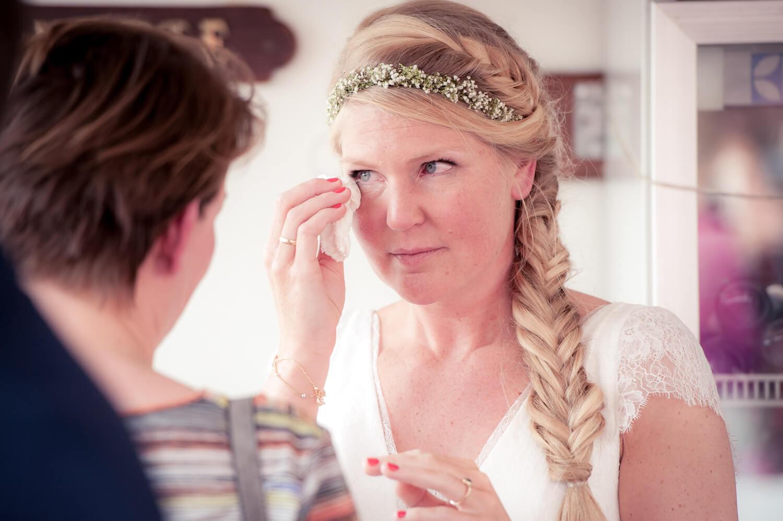 Braut tupft sich mit Taschentuch eine Freudenträne am Auge